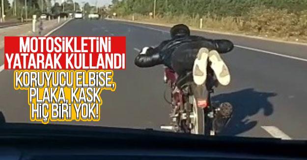 Motosikletini yatarak kullandı